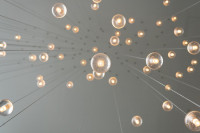 A visual representation of Innovation featuring a ceiling full of light bulbs.